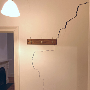 Photo of a wall next to an open doorway. There is a pendant light hanging down and coat hooks on the wall. The wall has a very large crack.