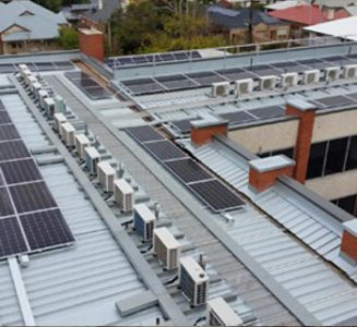 Image of industrial workplace re-roofing job with multiple solar panels