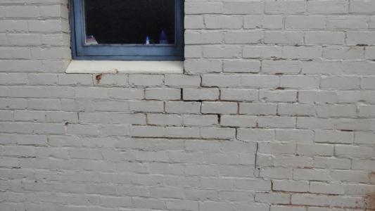 Cracked brick wall under a window frame
