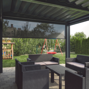 Outdoor pergola with outdoor setting. There is grass and a playground in the background.