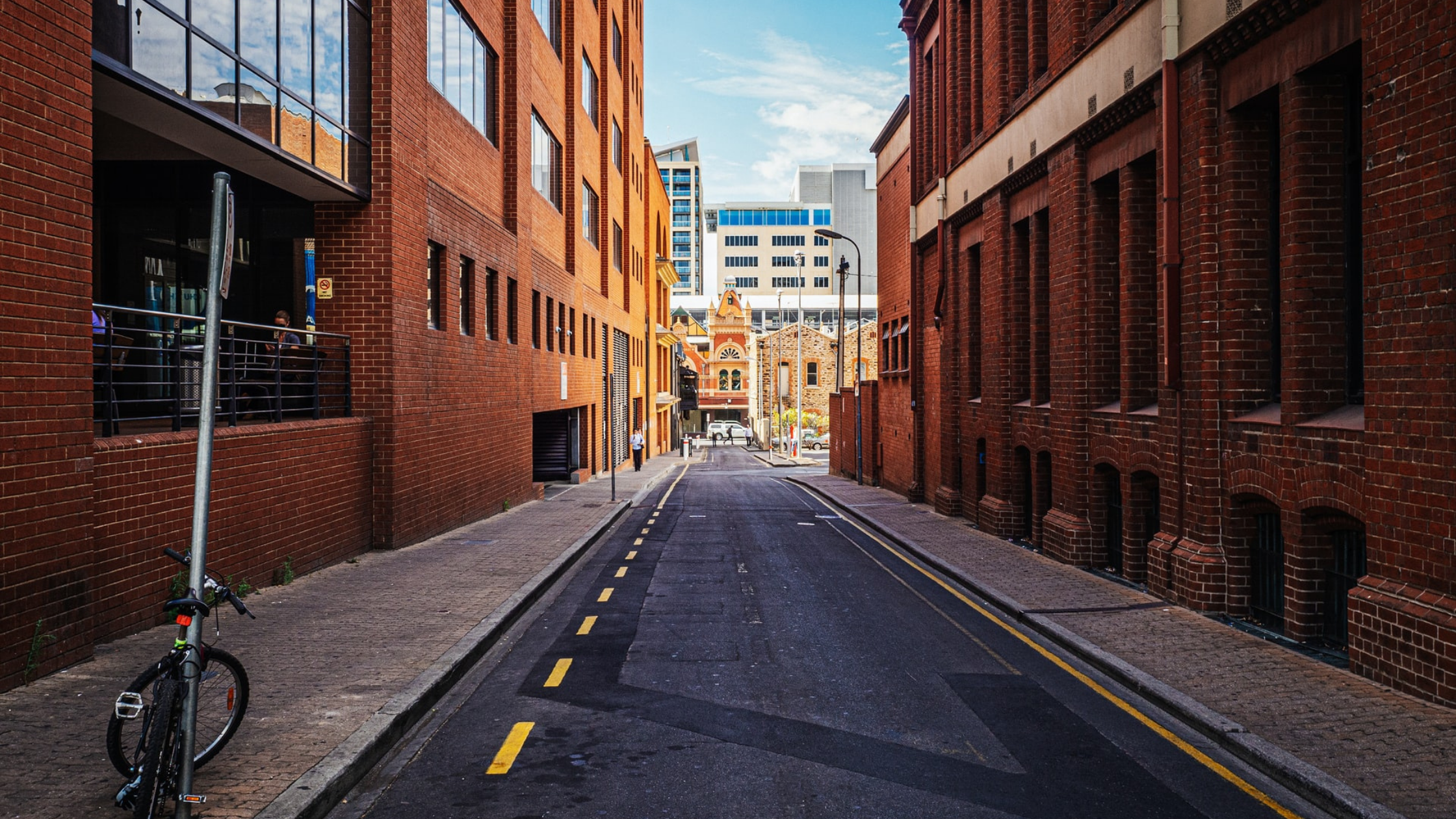 City alley between two red bricked buildings