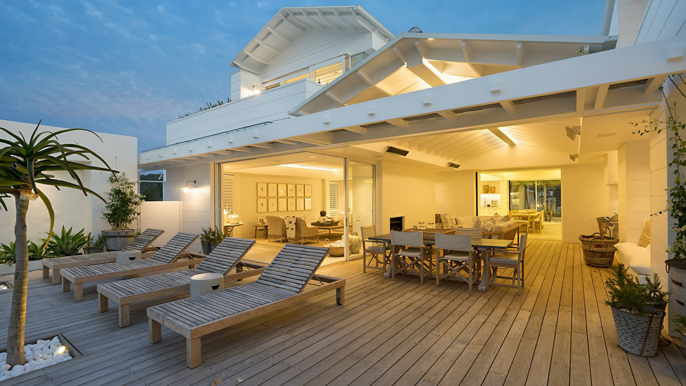 Outdoor entertaining area with timber decking and timber furniture with a white hamptons style house