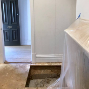 Loungeroom floor boards have been cut to gain access for internal underpinning of the foundation of a heritage home