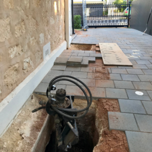 Pavers of a driveway have been pulled up and underpinning works in progress