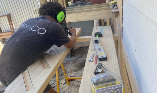 Carpenter cutting out knotches in a length of timber to make stairs for a deck